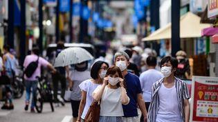 Des habitants de la ville de Tokyo, portant un masque dans la rue, le 1er août 2020. (PHILIP FONG / AFP)