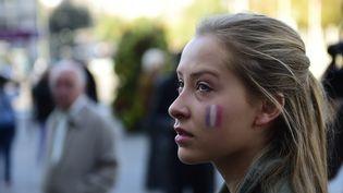 Le drapeau français peint sur la joue d'une jeune femme lors d'une minute de silence organisée devant la mairie de Madrid (Espagne). (PIERRE-PHILIPPE MARCOU / AFP)