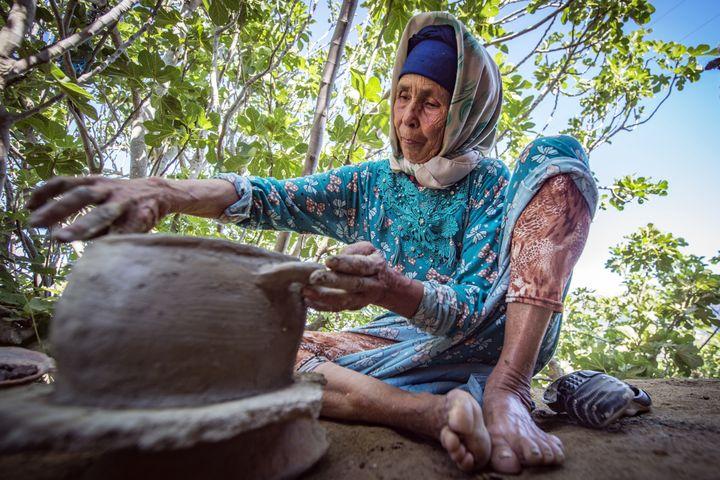 La potière marocaine Fatima Harama de la tribu des M'tioua travaille à la poterie près du village d'Ourtzagh dans la région de Taounate le 11 juin 2019. (FADEL SENNA / AFP)