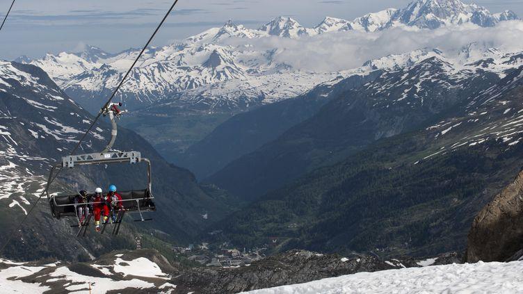 Les skieurs sont assis sur un téléski pour se rendre au sommet le jour de l'ouverture de la saison de ski d'été de Val d'Isère en Savoie, le 3 juin 2018. (ROMAIN LAFABREGUE / AFP)