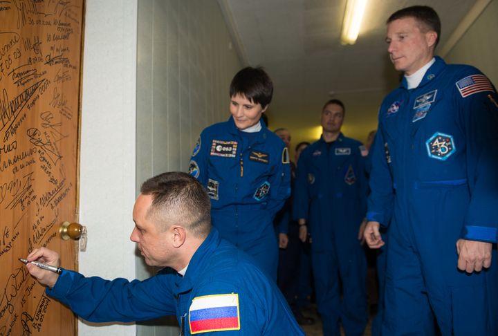 Le russe Anton Shkalperov signe, comme le veut la tradition, la porte de la chambre d'hôtel Cosmonaute Hotel, le 23 novembre 2014. (NASA/AUBREY GEMIGNANI /)