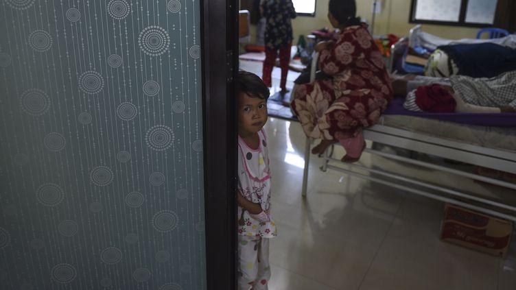 Une petite fille dans l'embrasure d'une porte, après le tsunamien Indonésie, le 25 décembre 2018. (MOHD RASFAN / AFP)