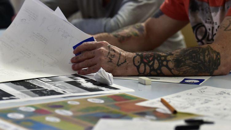 Un atelier BD en prison : des détenus créent des pages de bande dessinée pour le concours Transmurailles dans le cadre du Festival de la BD d'Angoulême.  (GEORGES GOBET / AFP)