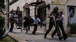 """15 janvier 2019 : les forces de sécurité kényanes aident des personnes à s'échapper après l'explosion d'une bombe à l'hôtel """"DusitD2"""" de Nairobi, au Kenya. (KABIR DHANJI / AFP)"""