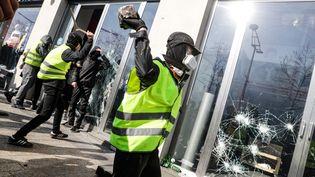 Des manifestants portant des gilets jaunes s'attaquent à la vitrine d'une enseigne d'habillement sur les Champs-Elysées, à Paris, le 16 mars 2019. (GEOFFROY VAN DER HASSELT / AFP)
