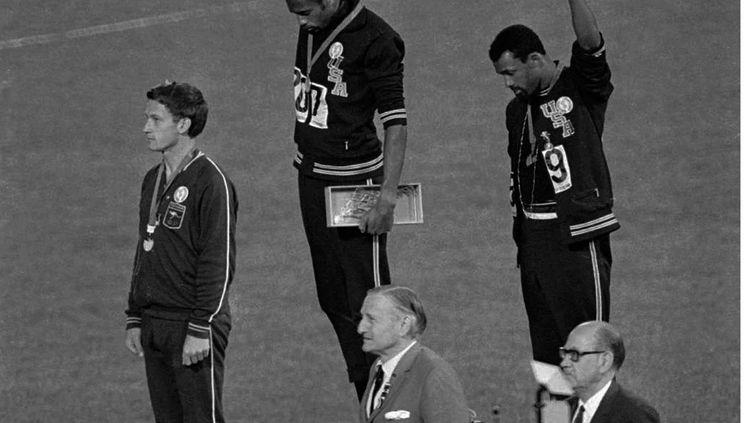 Les Américains Tommie Smith (au centre) et John Carlos (à droite) brandissent un poing ganté de noir sur le podium du 200 m aux Jeux olympiques de Mexico, le 16 octobre 1968. (AP / SIPA)