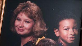 Dominique Theil et son fils aîné, Panama,il y a une vingtaine d'années. La photo figure en bonne place dans le salon de Dominique, à Napoleon (Michigan, Etats-Unis). (VALENTINE PASQUESOONE / FRANCEINFO)