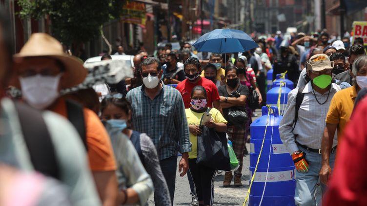 Des passants dans les rues de Mexico, le 6 juillet 2020. (HENRY ROMERO / REUTERS)
