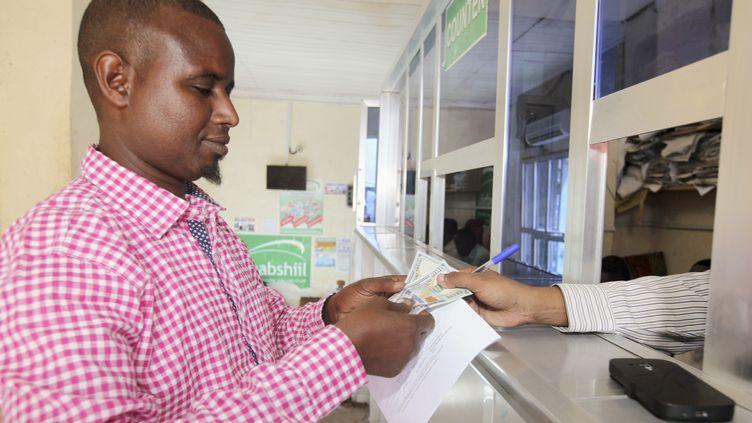Un client reçoit des dollars américains dans une agence de transfert d'argent à Mogadiscio, en Somalie, le 16 février 2015. (OMAR FARUK / REUTERS)