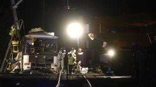 Des pompiers et des policiers sur les lieux de l'accident entre un car scolaire et un TER, à Millas, près de Perpignan (Pyrénées-Orientales), jeudi 14 décembre 2017. (RAYMOND ROIG / AFP)