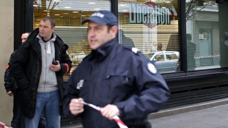 """Des policiers devant la rédaction du journal """"Libération"""", le 18 novembre 2013 à Paris. (THIBAULT CAMUS / AP / SIPA)"""