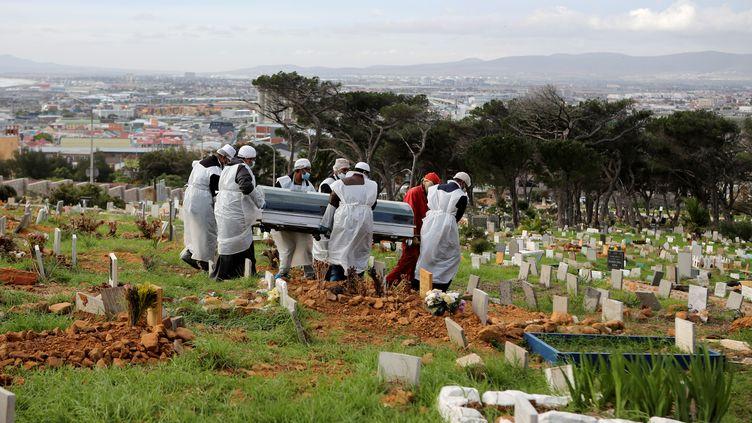 Dans un cimetière de Cape Town, sur la côte sud-ouest d'Afrique du Sud, des employés des pompes funèbres, masqués et revêtus de blouses, portent le cercueil d'un homme de 51 ans, mort du Covid-19 (photo prise le 12 mai 2020). (SUMAYA HISHAM / REUTERS)