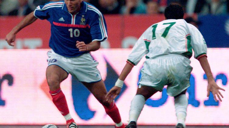 L'international français Zinedine Zidane et l'international algérien Slimane Raho lors du match amical France-Algérie le 6 octobre 2001 au Stade de France. (OLIVIER MORIN / AFP)