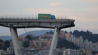 Un camion arrêté au bord du gouffre sur le pont Morandi qui s'est effondré, le 14 août 2018 à Gênes (Italie). (VALERY HACHE / AFP)