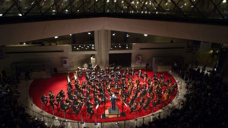 Pierre Boulez dirige l'Orchestre de Paris sous la pyramide du Louvre, le 20 décembre 2011. (MIGUEL MEDINA / AFP)