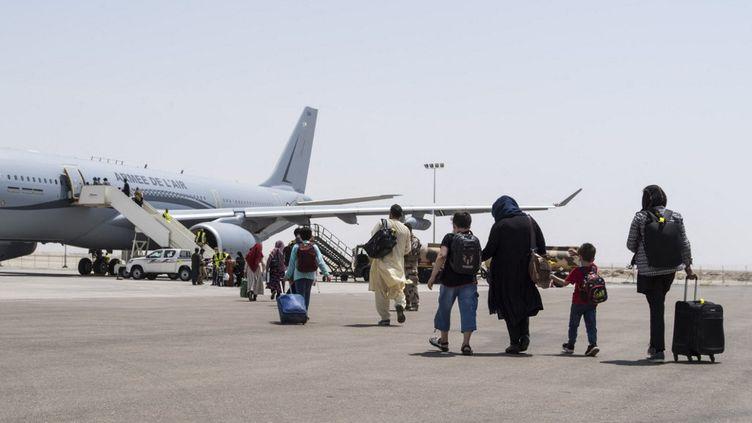 Une photo diffusée par l'état-major des armées montre des Afghans embarquant dans un Airbus A330 français à Abou Dhabi, à destination de l'aéroport de Roissy, le 20 août 2021. (ETAT MAJOR DES ARMEES)