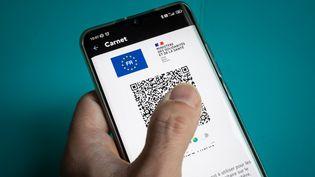 Une personne montre son pass sanitaire sur un smartphone, le 11 octobre 2021. (RICCARDO MILANI / HANS LUCAS / AFP)