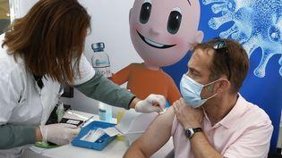 Une soignante vaccine un homme contre le Covid-19 à Tel-Aviv, le 3 janvier 2021. (JACK GUEZ / AFP)