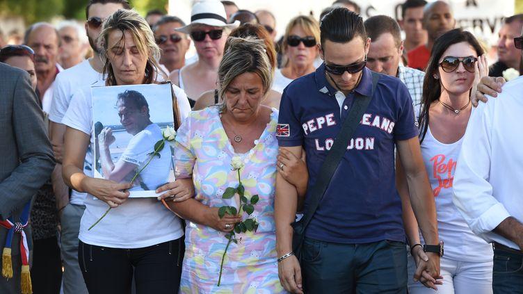 Kevin etLaurence (au centre)Cornara, le fils et la femme d'HervéCornara, lors d'une marche à Fontaines-sur-Saône(métropole de Lyon), le30juin2015. (PHILIPPE DESMAZES / AFP)