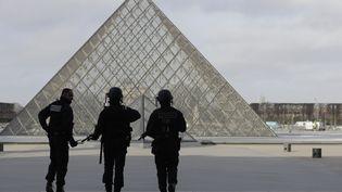 Des policiers devant la pyramide du Louvre après l'agression de militaires, le 3 février 2017. (CHRISTIAN HARTMANN / REUTERS)