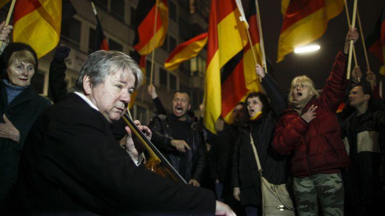 Le musicien Thomas Beckmann joue du violoncelle pour montrer son opposition à des manifestants anti-islam devant lui, le 12 janvier 2015, à Düsseldorf (Allemagne). (INA FASSBENDER / REUTERS)