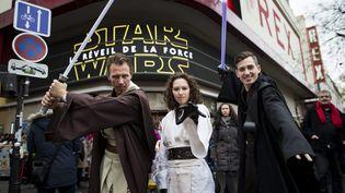 """Des fans de """"Star Wars"""" posent en costume à la sortie d'uneséance du """"Réveil de la Force"""", le 16 décembre 2015, devant le Grand Rex, à Paris. (MAXPPP)"""