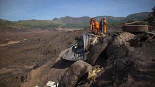 Des pompiers s'affairent dans les décombres du barrage de Brumadinho (Brésil), le 31 janvier 2019. (MAURO PIMENTEL / AFP)