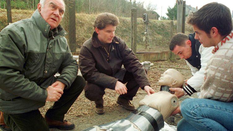 Le juge d'instruction du tribunal de Châteauroux, Jean Dematteis (au milieu), observe, le 14 janvier 2000 sur les voies de la gare de Chabenet, en compagnie de Rémy Julienne (à gauche), le mannequin qui doit servir pour la reconstitution du meurtre d'Isabel Peake. (MEHDI FEDOUACH / AFP)