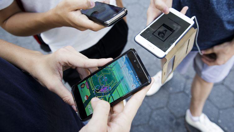 """Des personnes jouent à """"Pokémon Go"""", le 11 juillet 2016, à New York. (MAXPPP)"""