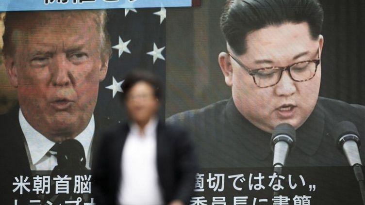 Les visages du président américain, Donald Trump, etdu leader nord-coréen, Kim Jong-un, sur un écran géant à Tokyo (Japon), le 25 mai 2018. (BEHROUZ MEHRI / AFP)
