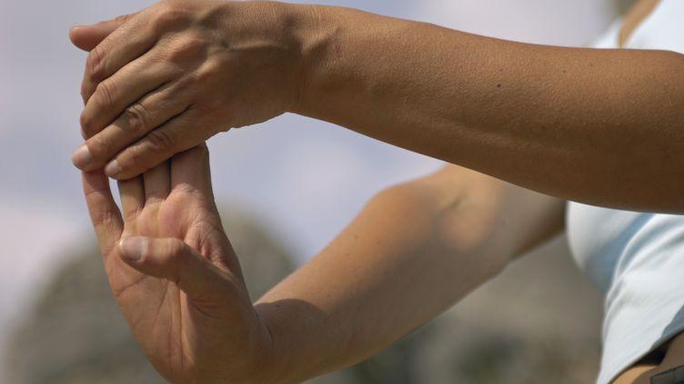 """Une jeune femme étire ses mains. Selon les observations d'un allergologue californien, relayées le 30 mars 2012 par """"Le Monde"""", elle ne risque pas d'arthrose. (DORLING KINDERSLEY / GETTY IMAGES)"""