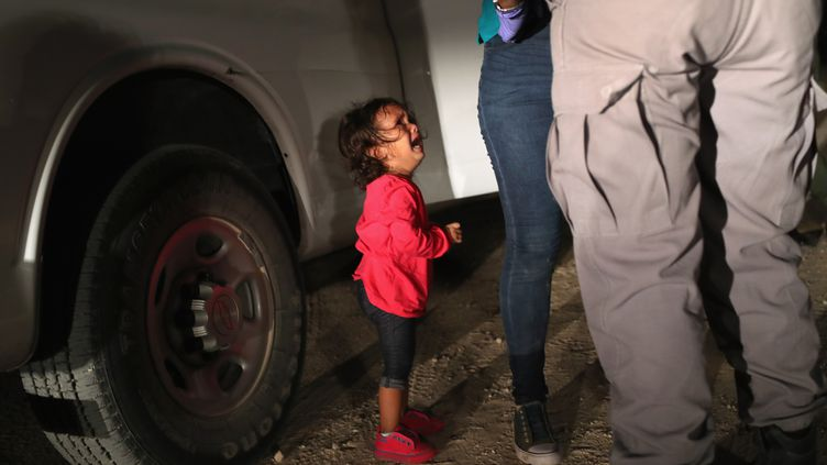 Une petite fille hondurienne de 2 ans, en pleurs alors que sa mère est fouillée par les patrouilles de sécurité aux frontières, à McAllen, au Texas, le 12 juin 2018. (JOHN MOORE / GETTY IMAGES / AFP)