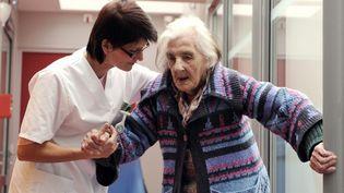 Une aide-soignante s'occupe d'une personne âgée, le 4 décembre 2010, dans une maison spécialisée à La Rochelle (Charente-Maritime). (XAVIER LEOTY / AFP)