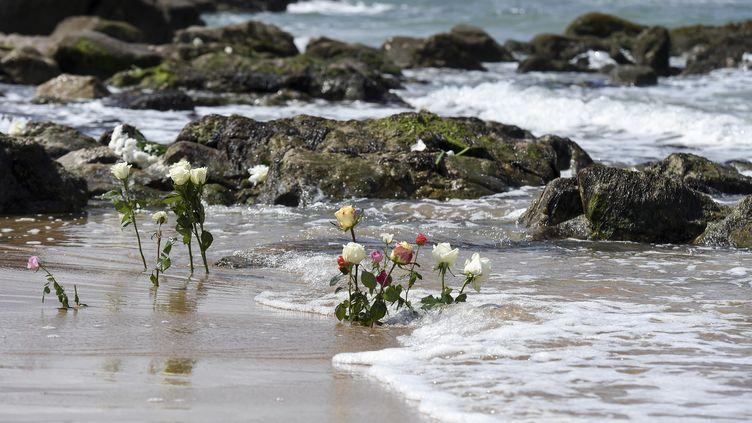 Des fleurs plantées dans le sable, en hommage aux trois sauveteurs de la SNSM morts en mer, le 10 juin 2019 aux Sables d'Olonne (Vendée). (SEBASTIEN SALOM-GOMIS / AFP)