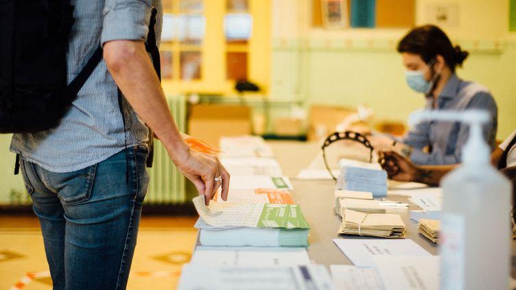Un électeur dans un bureau de vote dans le 11e arrondissment de Paris, lors du premier tour des élections départementales et régionales, dimanche 20 juin 2021. (DELPHINE LEFEBVRE / HANS LUCAS / AFP)
