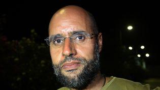 Photo d'archive prise le 23 août 2011 qui montre Seif al-Islam, le fils de feu le dictateur libyen Mouammar Kadhafi, devant des partisans et des journalistes dans le complexe résidentiel de son père à Tripoli, la capitale libyenne. (IMED LAMLOUM / AFP)