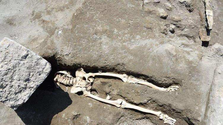 Le squelette d'un homme décapité par un bloc de pierre est excavé sur le site archéologique de Pompéi, en Italie, le 30 mai 2018. (PARQUE ARQUEOLOGICO DE POMPEYA / NOTIMEX / AFP)