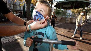 Un homme met un masque à un enfant, dans une commune du Var, le 11 novembre 2020. (PH ARNASSAN / MAXPPP)