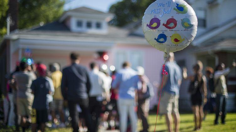 """Un ballon avec le message """"Tu nous manques"""" est brandi devant la maison d'enfance de Mohamed Ali, le 9 juin 2016 à Louisville (kentucky). (JIM WATSON / AFP)"""