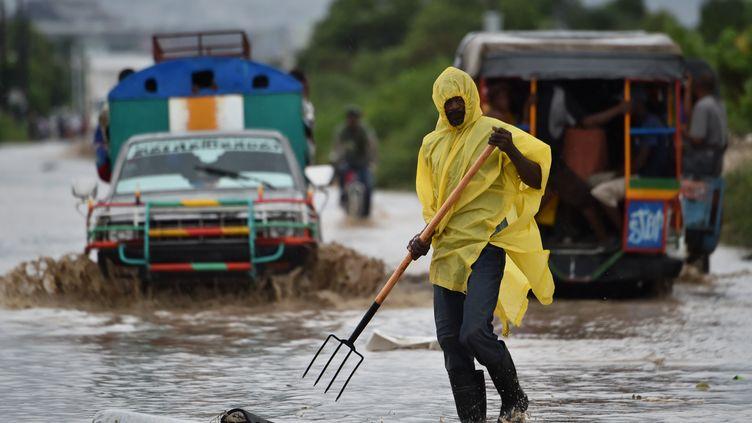 Un homme nettoie les ordures emportés par l'ouragan dans les rues de Port-au-prince (Haïti), le 4 octobre 2016. (HECTOR RETAMAL / AFP)