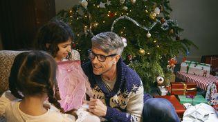 Un papa et ses deux filles ouvrant les cadeaux de Nöel dans le salon le 9 /09/2014. (FRANK AND HELENA / CULTURA CREATIVE)