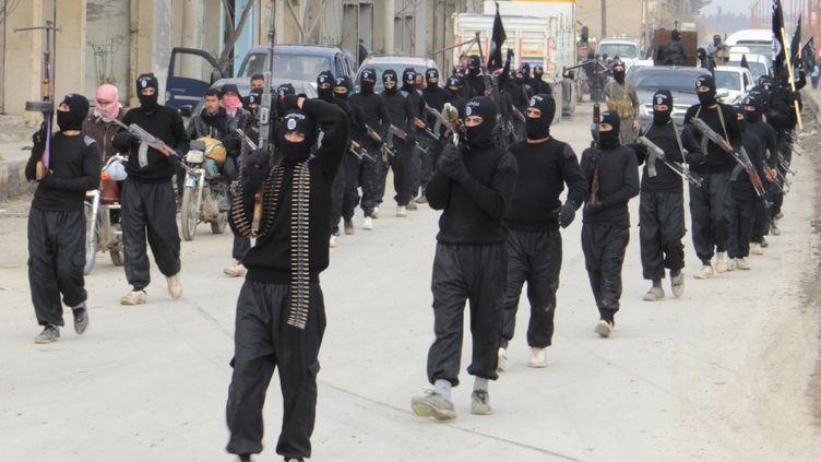 Des combattants de l'Etat islamique en Irak et au Levant paradent dans les rues de Tel-Abyad (Syrie), près de la frontière turque, le 2 janvier 2014. (REUTERS)