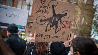 """Une manifestante brandit une pancarte lors de la mobilisation contre la proposition de loi sur la """"sécurité globale"""" à Metz, le 5 décembre 2020. Photo d'illustration. (NICOLAS BILLIAUX / HANS LUCAS)"""