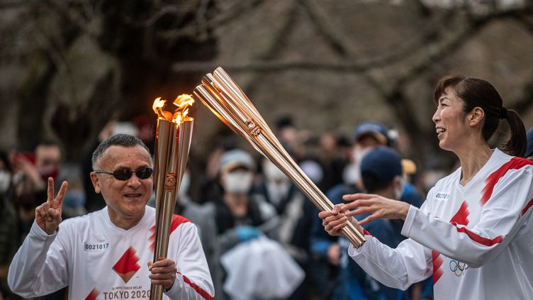 Relais de la flamme olympique entre Masamitsu Kikuchi et Motoko Obayashi, le 26 mars 2021.  (PHILIP FONG / AFP)