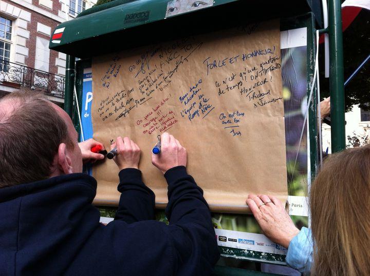 Des participants à la manifestation de soutien à Nicolas,l'opposant au mariage des homosexuels condamné à deux mois de prison ferme, lui écrivent des messages de soutien, le 23 juin 2013 à Paris. (BENOIT ZAGDOUN / FRANCETV INFO)