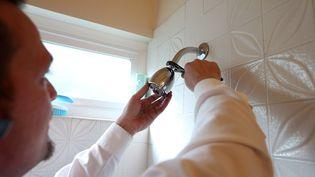 Un plombier change un pommeau de douche. (JUSTIN SULLIVAN / GETTY IMAGES NORTH AMERICA)