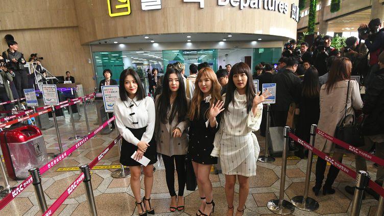 """Les membres du groupe de K-pop """"Red velvet"""" posent dans le hall des départs de l'aéroport de Séoul le 31 mars 2018 avant leur départ pour Pyongyang. (JUNG YEON-JE / AFP)"""