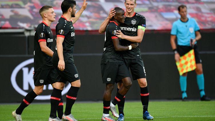 Moussa Diaby (Bayer Leverkusen) félicité par ses coéquipiers après son but en huitième de finale retour de la Ligue Europa contre les Glasgow Rangers (SASCHA SCHUERMANN / AFP)
