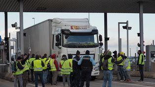 """Des """"gilets jaunes"""" laissent un conducteur passer gratuitement à un péage sur l'autoroute A10, à Blois (Loir-et-Cher), le 24 novembre 2018. (GUILLAUME SOUVANT / AFP)"""