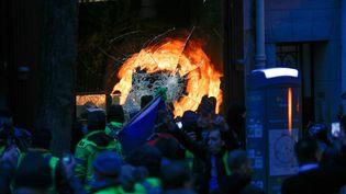 """Des manifestants devant une vitrine brisée lors de """"l'acte III"""" de la mobilisation des """"gilets jaunes"""", le 1er décembre 2018 à Paris. (GEOFFROY VAN DER HASSELT / AFP)"""